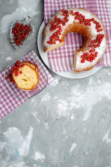 Вид сверху вкусный круглый торт со свежей красной клюквой и клюквенным соком на белом столе, печенье, чайная ягода