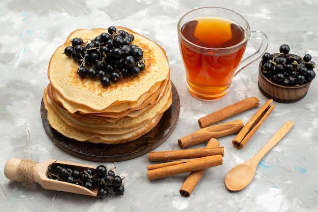 Вид сверху вкусные круглые блины, вкусные и круглые, сформированные с черникой и корицей на светлом столе для приготовления блинов