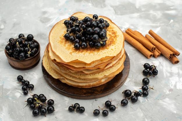 ライトデスクでブルーベリーとシナモンで形成されたおいしい丸いおいしいパンケーキのトップビュー
