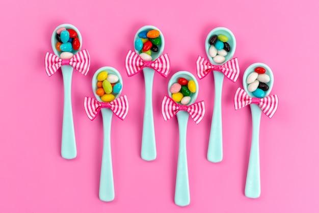 Вид сверху разноцветных конфет внутри зеленых ложек с бантом на розовом сладком радужном сахаре