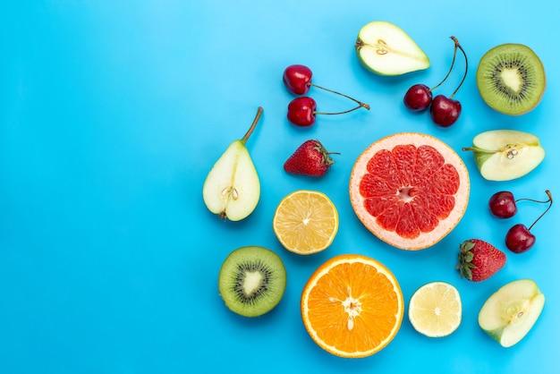 Вид сверху на разные фруктовые композиции, нарезанные свежими на синем, фруктовом цитрусовом цвете витамина