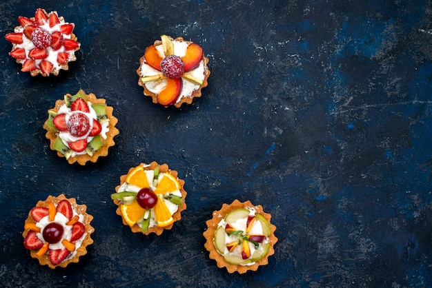 Вид сверху разные маленькие пирожные со сливками и свежими нарезанными фруктами на синем фоне фруктовый торт, печенье, чай, сахар