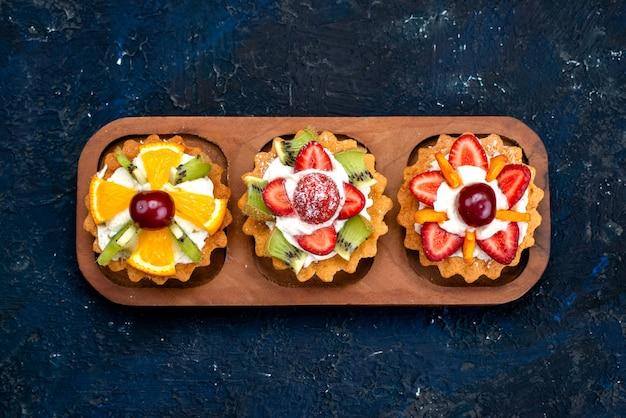 青い背景のフルーツケーキビスケットティーのクリームと新鮮なスライスしたフルーツの上面図別の小さなケーキ