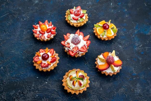 Вид сверху разные маленькие пирожные со сливками и свежими нарезанными фруктами на синем фоне фруктового бисквита