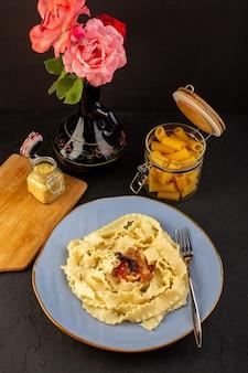平面図の生地パスタは、デザインされたカーペットと水差しの中のワインと花のグラスで丸い青いプレートの内側においしい塩漬けのおいしい塩漬けのイタリア料理料理を調理しました