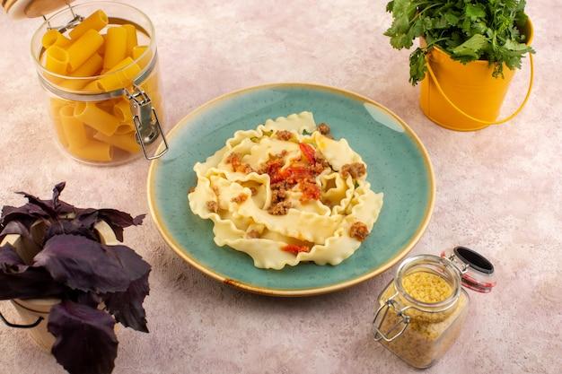 上面図生地パスタは肉野菜で美味しく調理し、ピンクの机の上の花と生パスタと丸いグリーンプレートの内側に塩漬け