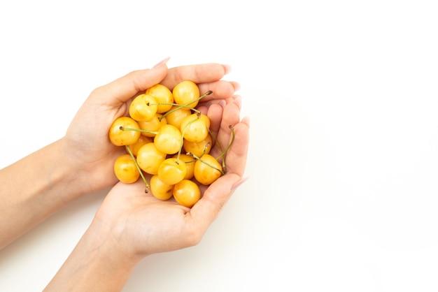 白、フルーツ色の夏にサクランボのまろやかで甘い果物を保持している女性のトップビュー