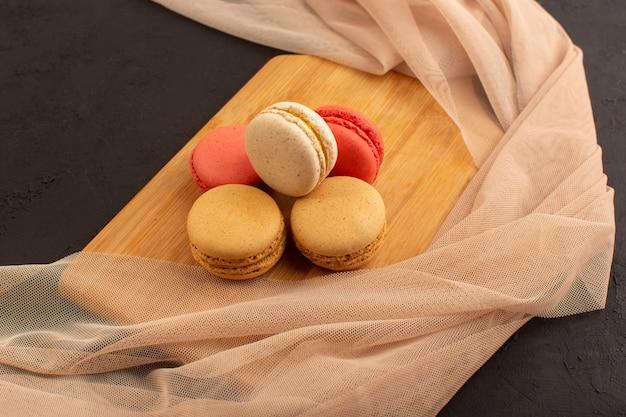 Вид сверху французские макароны вкусные и круглые, сформированные на темном столе, торт, бисквит, сладкий