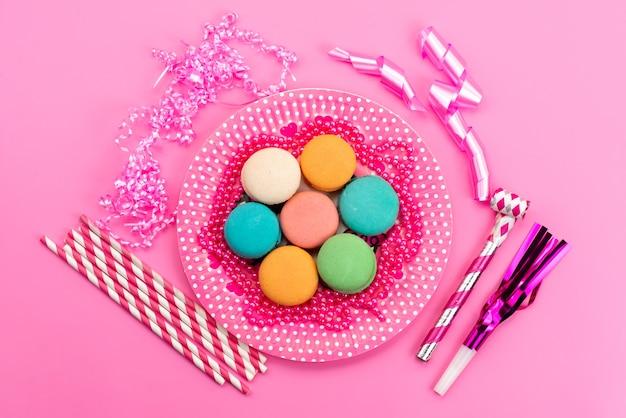 Вид сверху французские макароны внутри розового цвета, тарелка с конфетами в форме палочки, свисток на день рождения на розовом, кондитерские изделия из бисквитного торта