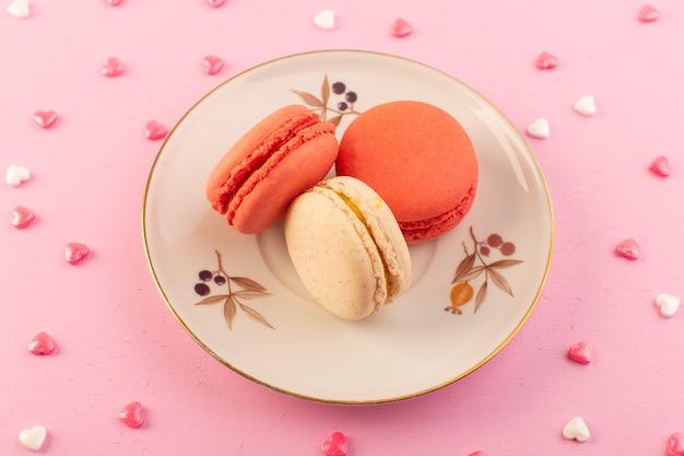 ピンクのテーブルケーキビスケットシュガースイートの丸皿の中のトップビューフランスのマカロン