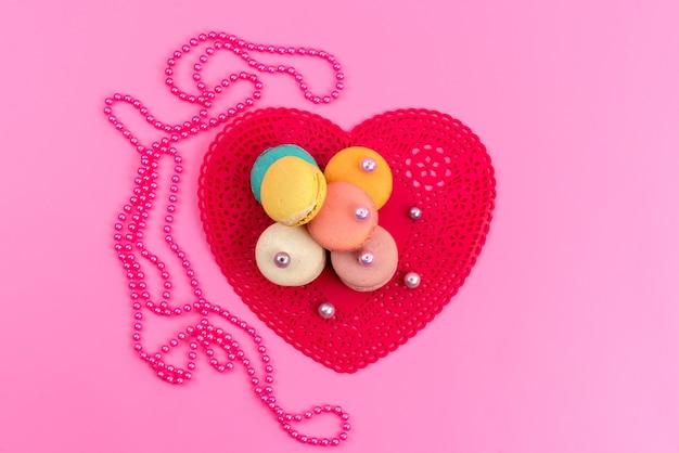 Вид сверху французские макароны круглые вкусные вместе с красной формой в форме сердца на розовом, сладком пироге