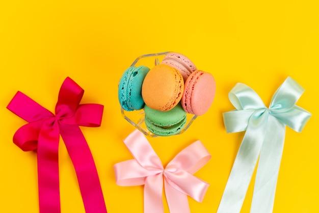 Вид сверху французские макароны круглые сладости с красочными бантами на желтом, сладкий сахарный торт кондитерский