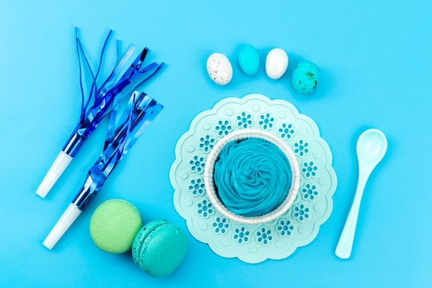 Вид сверху французские макароны со свистками на день рождения, яйца на синем, кондитерские изделия из бисквитного торта