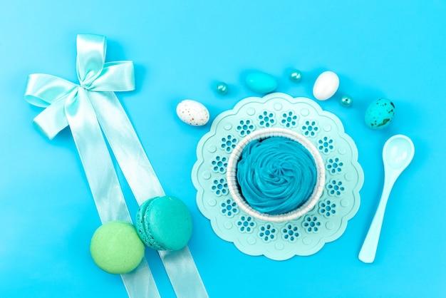 Вид сверху французские макароны с разноцветными белыми яйцами, пластиковая ложка на синем, цвет бисквитного торта