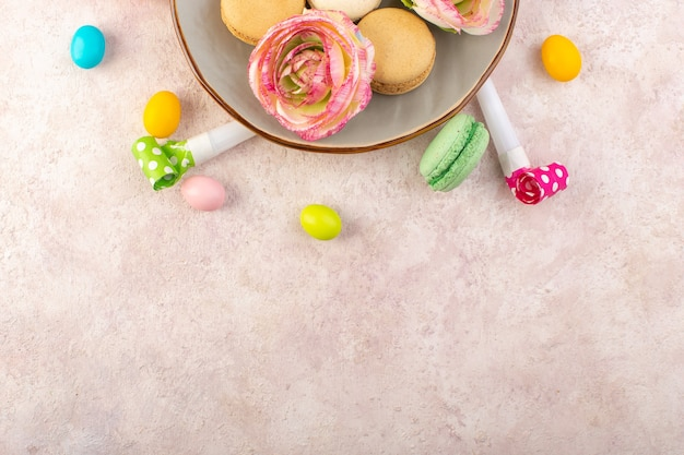Вид сверху французские макароны с розами и конфетами на розовом столе, торт, бисквит, сладкий
