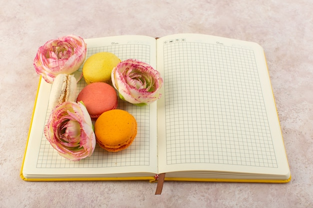 Вид сверху французские макароны с розами в тетрадке и розовым столовым пирогом, бисквитным сахаром