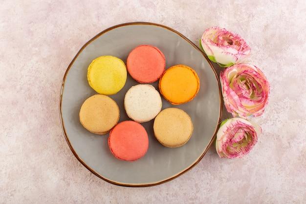 Вид сверху французские макароны с розами на розовом столе, торт, бисквит, сладкий
