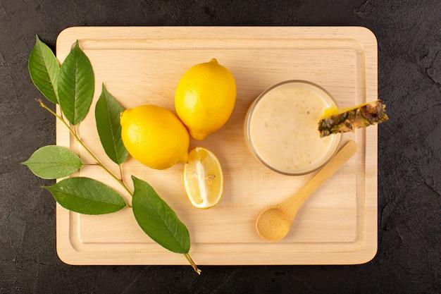 暗い背景に黄色のレモンと一緒に木製のクリームの机の近くの小さなガラスの中のトップビュー新鮮なカクテルおいしい冷却ドリンク
