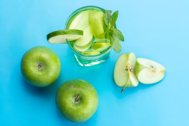 Вид сверху коктейль из свежих фруктов с кусочками свежих фруктов, охлаждающий льдом на синем, коктейль из сока, фруктовый цвет