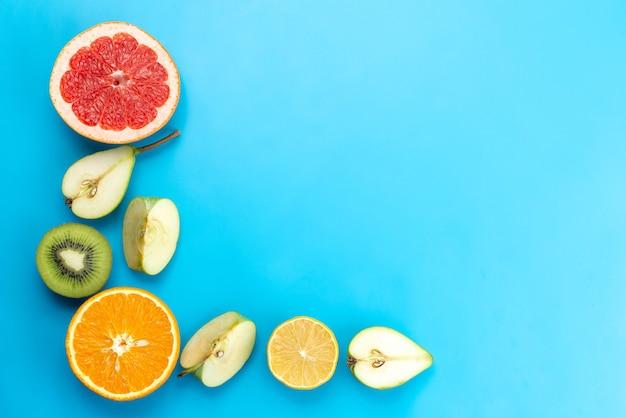 Композиция свежих фруктов, вид сверху, нарезанная спелыми и спелыми на синем, фруктовом цвете, витамине
