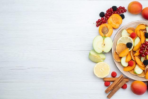 トップビューの新鮮な果物のカラフルで熟した木製の机と白い背景の果物色の食品写真