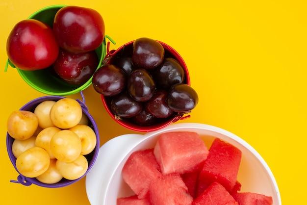 Вид сверху свежие фрукты, такие как желтые и красные вишни, сливы и арбуз на желтом, фруктовом летнем цвете