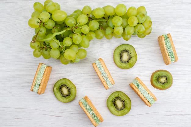 トップビューフレッシュグリーンブドウサワージューシーでまろやかな、白い背景のフルーツ熟した植物のクッキーとキウイ