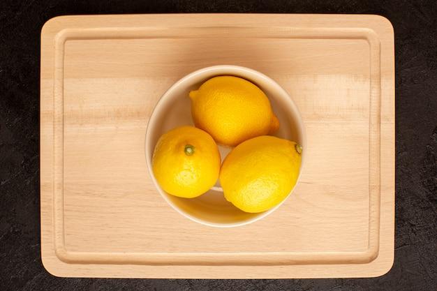 Вид сверху свежие лимоны кислые спелые внутри белая тарелка весь мягкий цитрусовый тропический витамин желтый на темном столе