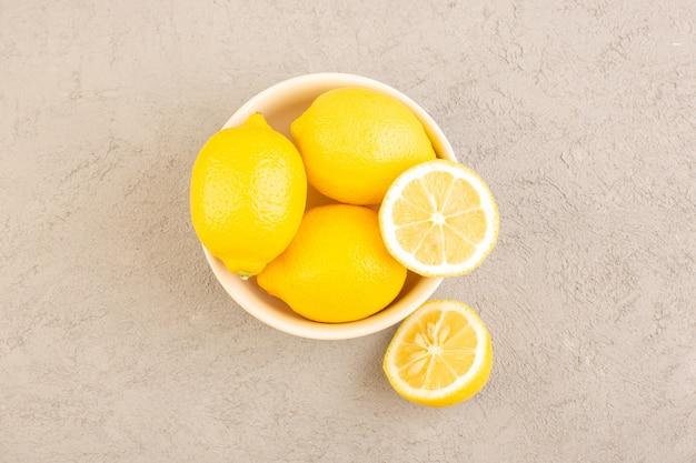 Вид сверху свежие лимоны кислые спелые целые цитрусовые тропические витаминно-желтые вместе с сухими цветами на столе крем
