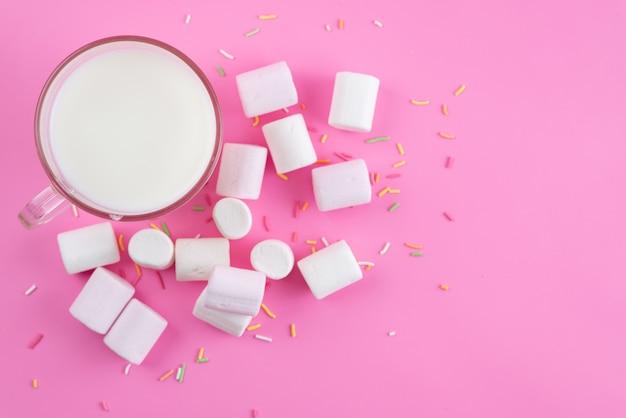 Вид сверху: свежее молоко и белый зефир на розовых сладких конфетах.