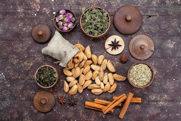 Вид сверху свежие соленые и вкусные орехи вместе с корицей на темных деревянных орехах для закусок