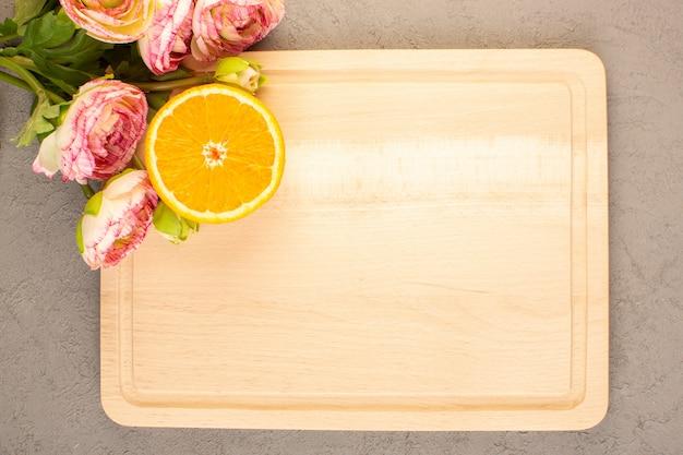 Вид сверху свежих апельсинов с кисло-спелыми ломтиками и целого сочного цитрусового тропического витаминно-желтого цвета на кремовом столе
