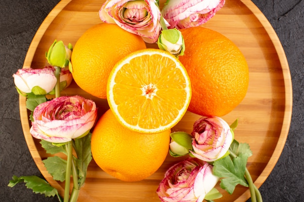 トップビューフレッシュオレンジサワー熟した全体と暗い机の上に黄色い乾燥したバラの芳醇な柑橘類のトロピカルビタミンイエローでスライス