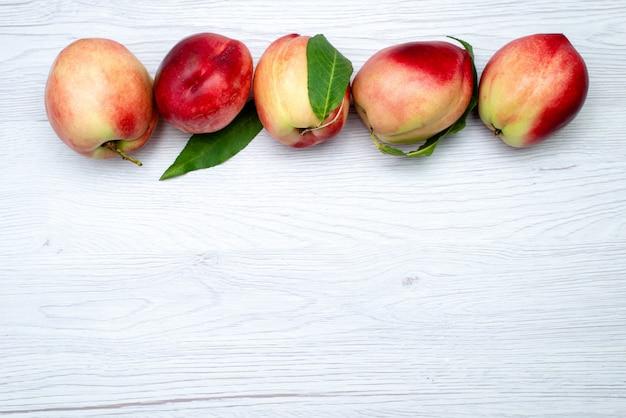 トップビューの新鮮な桃の酸味とまろやかな白い背景のフルーツ色の新鮮