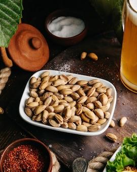 トップビューの新鮮なピーナッツ、グリーンサラダ、木製デスクスナックナッツ写真