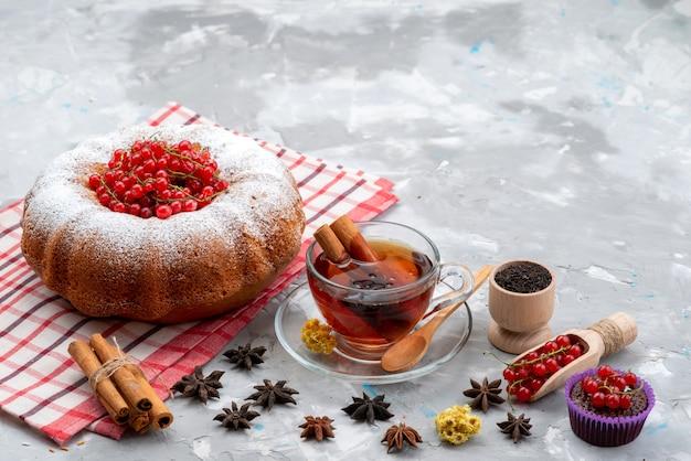 トップビューフレッシュな赤いクランベリーの酸味とまろやかなラウンドケーキティーとシナモンホワイトデスクフルーツベリー