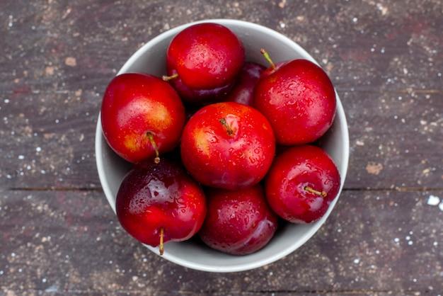 Вид сверху свежие красные сливы, спелые и спелые внутри белой тарелки на деревянном столе, фруктовый сок из мякоти