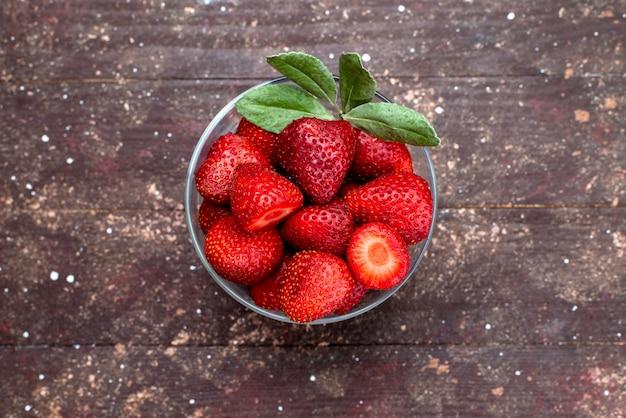 Вид сверху свежей красной клубники спелой и сочной внутри круглой миски на коричневом фоне ягодные фрукты свежий цвет красный