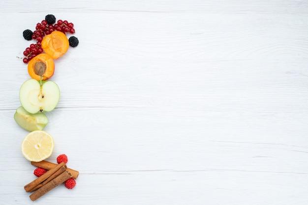 トップビューフレッシュスライスフルーツカラフルでシナモンと熟した白い背景の果物色食品写真