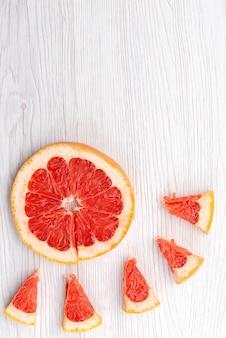 Вид сверху свежий нарезанный грейпфрут, мягкий и сочный на белом, фруктовом цитрусовом цвете