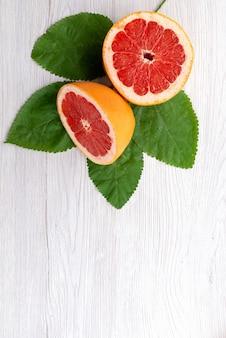 Вид сверху свежего нарезанного грейпфрута с зелеными листьями на белом, сок цитрусовых