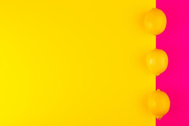 Вид сверху свежие желтые лимоны спелые сочные спелые целые выложены на розово-желтый