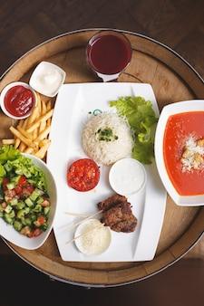 Вид сверху жареного мяса вместе с рисовым свежим салатом, томатным супом и вишневым соком на коричневом деревянном столе