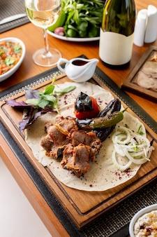 Вид сверху жареные мясные кости с жареными овощами, белое вино и соус на столе, еда, ужин, ужин, ресторан