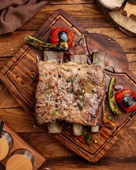 Вид сверху жареного мяса с овощами на коричневом деревянном столе.