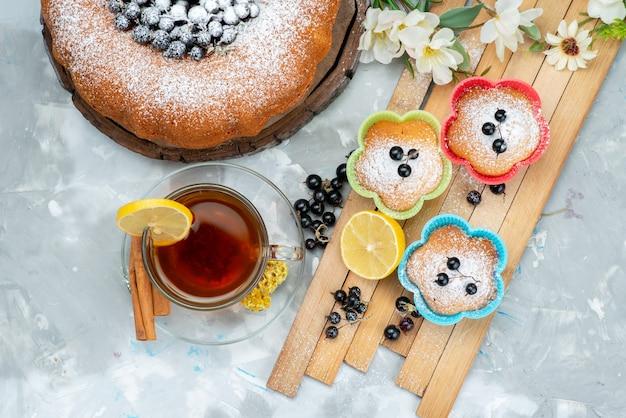 Фруктовый торт, вид сверху, восхитительный и круглый, сформированный со свежими синими ягодами и чашкой чая на ярком торте