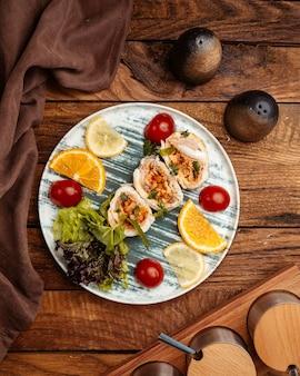 Вид сверху на ломтики фруктов, таких как апельсин и лимон, внутри тарелки на коричневом деревянном столе, свежие фрукты для здоровья