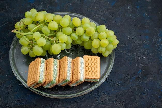 トップビューグレープ風味のクッキーサンドイッチクッキーダークデスクフルーツケーキのプレート内部の新鮮な緑のブドウ