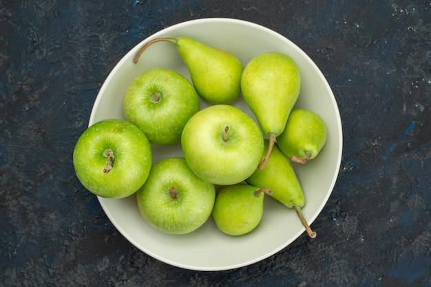 Вид сверху зеленые яблоки с грушами внутри белой тарелки на темном фоне фруктовой мякоти свежей