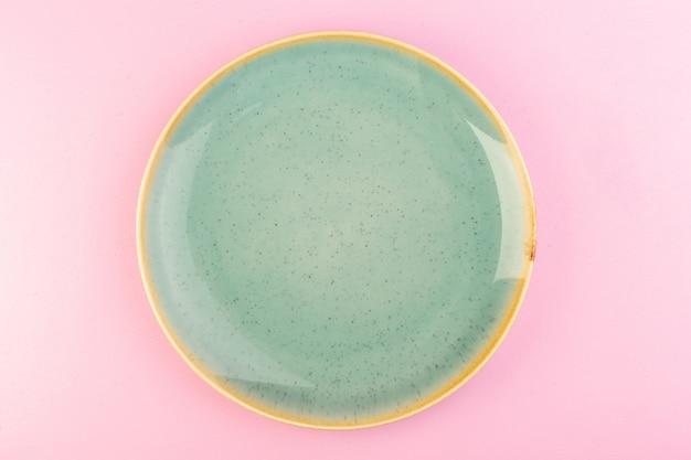 Зеленая пустая тарелка, вид сверху, сделанная для еды на розовом